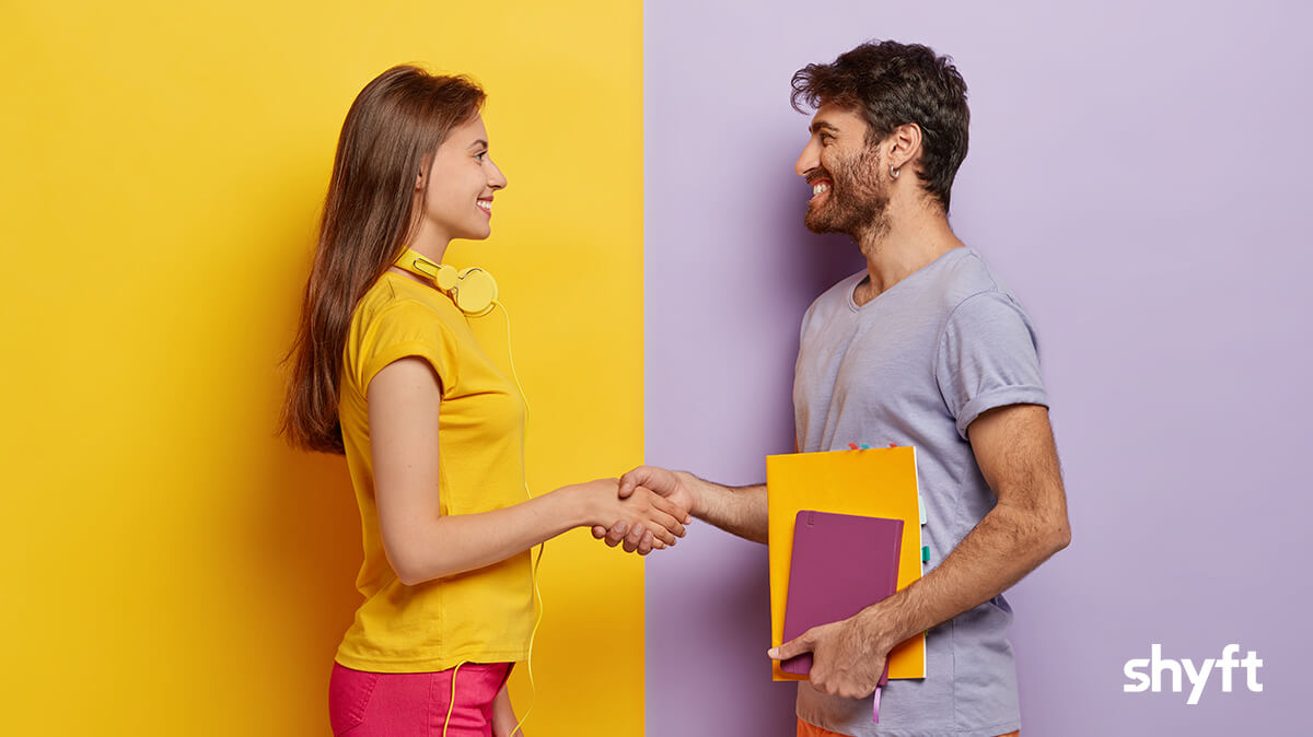 A man and a woman smiling and shaking hands while meeting