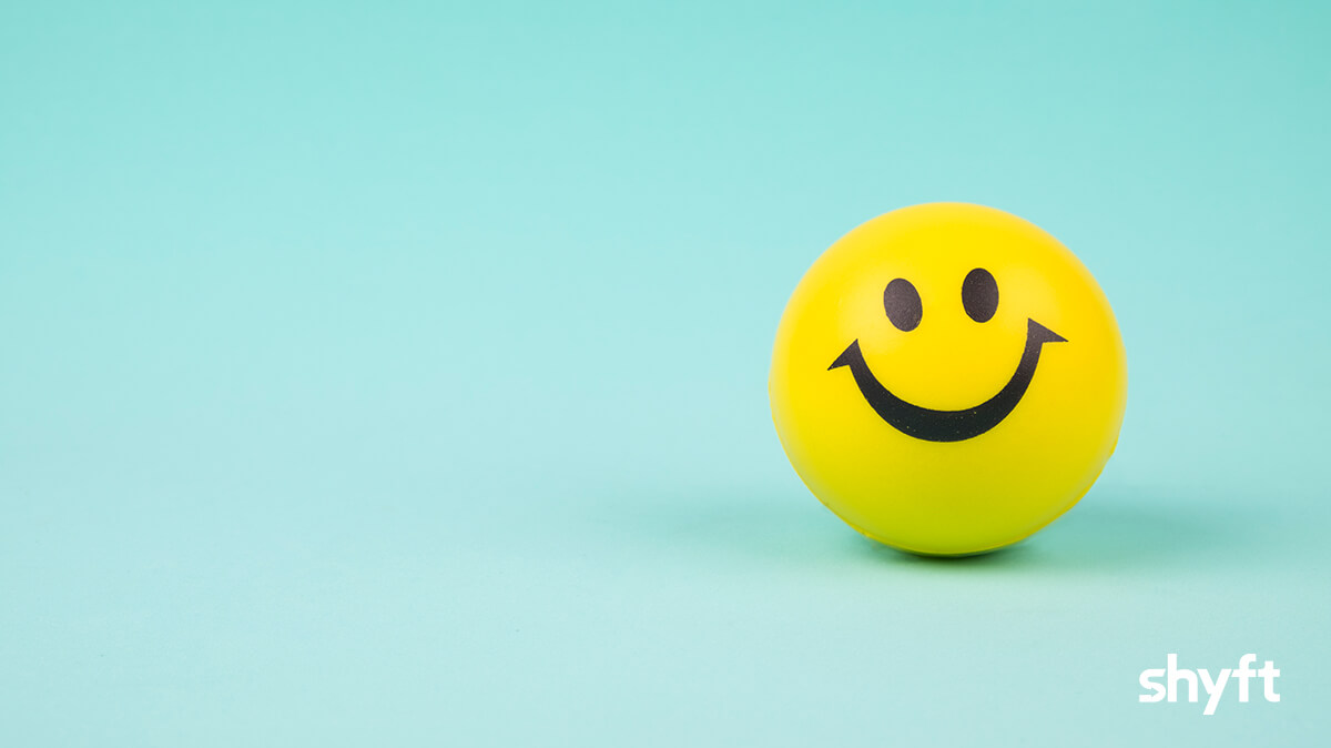 A yellow stress ball with a smiley face against a light turquoise background