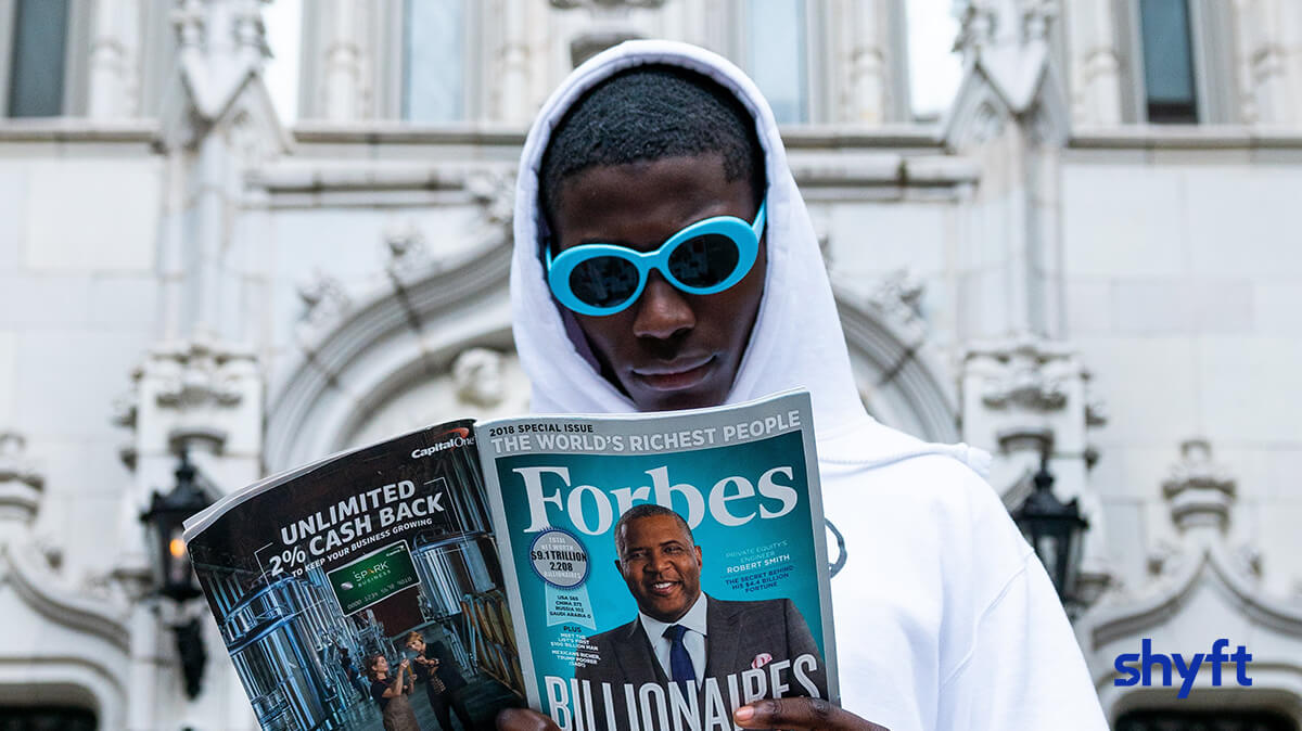 A man with designer sunglasses, wearing a hoodie, standing in front of his mansion and reading a Forbes magazine