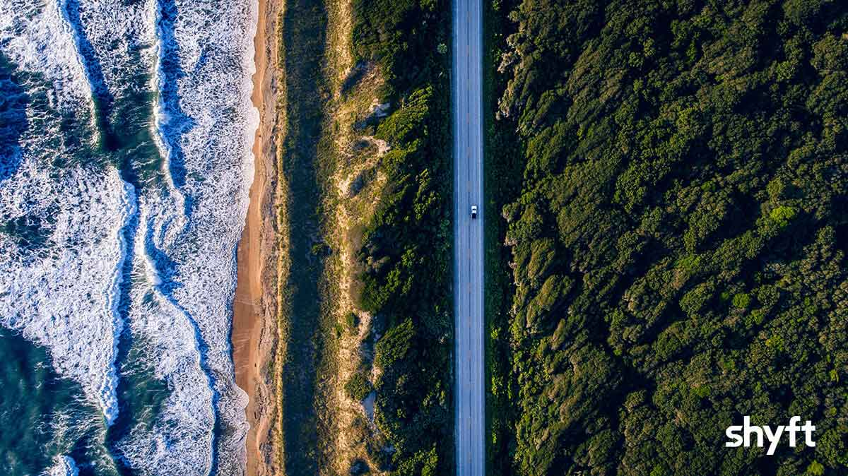 Bird's-eye view of a car on the road between a seaside and a forest