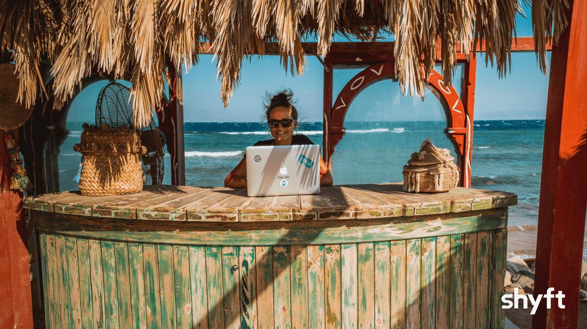 Happy digital nomad working on her laptop behind a tiki bar by the beach