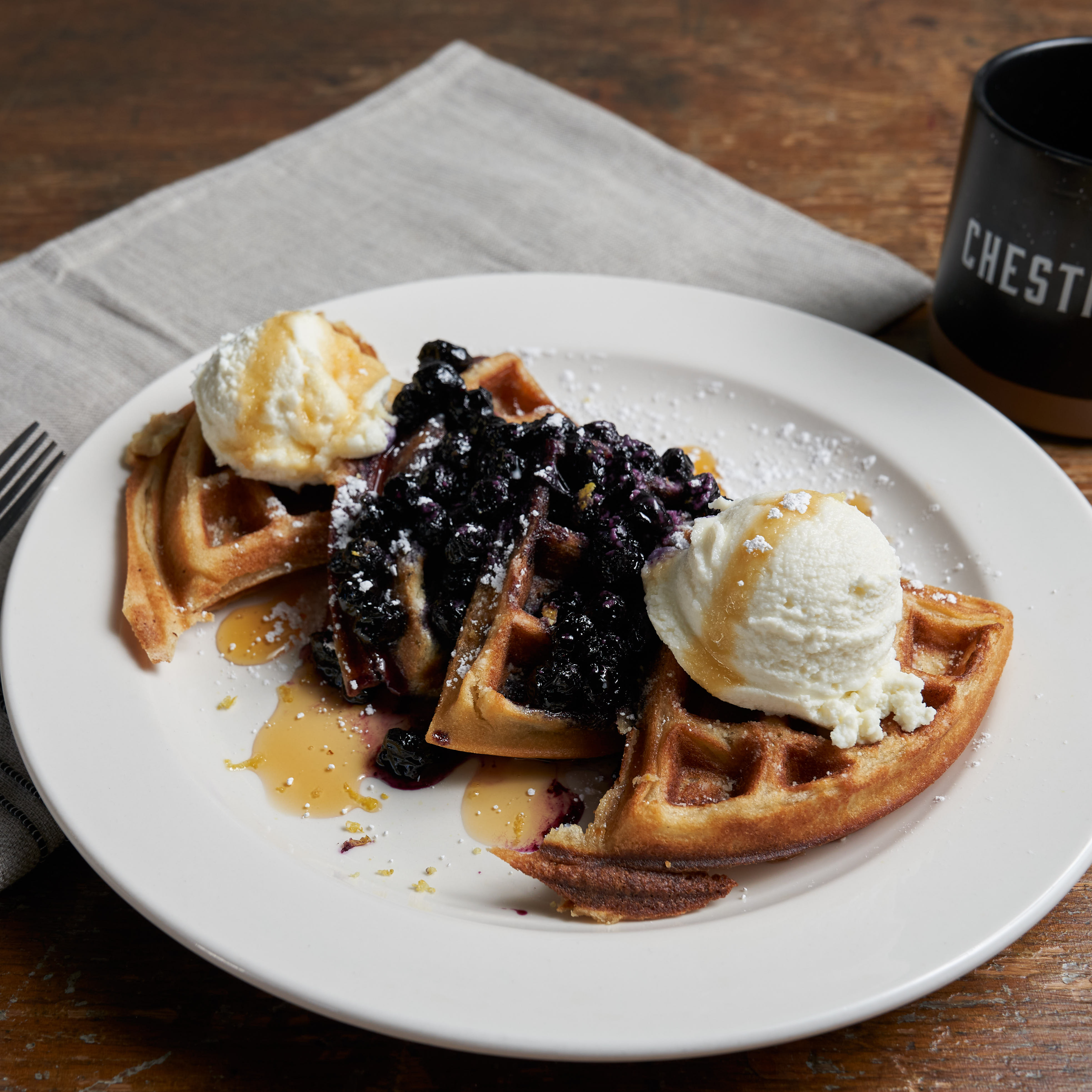 Pictured is the lemon ricotta waffles covered in a blue berry compote with whipped cream and coffee