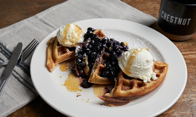 On a plate is the lemon ricotta waffles covered in whipped cream, fresh blue berries, and a blue berry compote. On the side is silverware and a cup of coffee