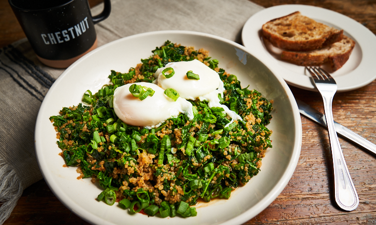 In a bowl is sautéed kale, quinoa, and two poached eggs on top of a spicy siracha sauce