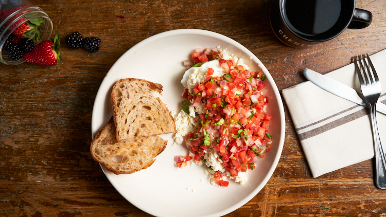On this dish is pictured a plate. On the left side of the plate is toast and on the right is the Huevos Avocados. A whole avocado cut in hald with a poached egg in each half covered in feta cheese and pico de gallo