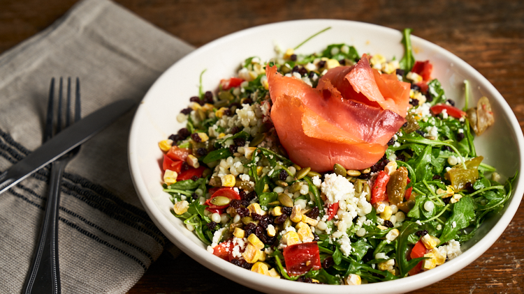 This images pictures the Phoenix Chopped Salad containing arugula, freeze dried corn, sautéed peppers, feta, dried currants, israeli couscous, pumpkin seeds & lox salmon tossed in a creamy pesto dressing