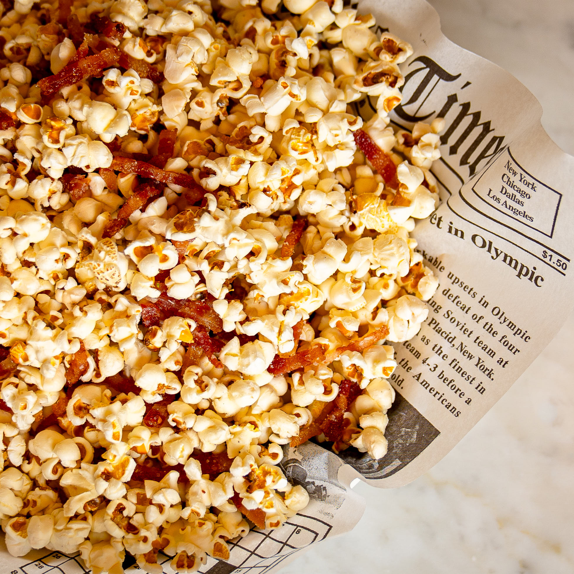 Pictured is a basket of popcorn and sliced bacon