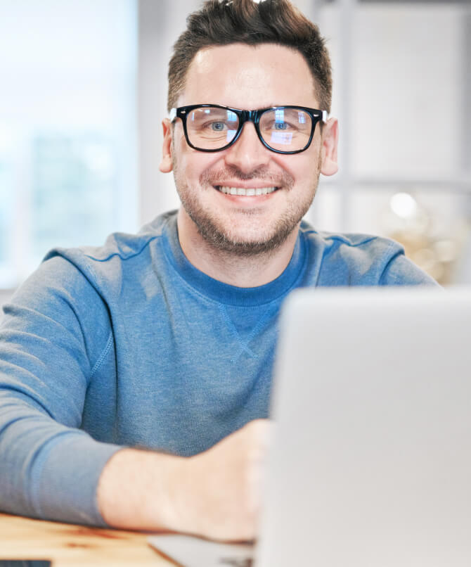 Man with glasses on Macbook Pro