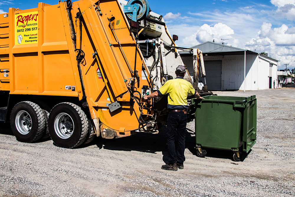 Waste truck with man standing beside