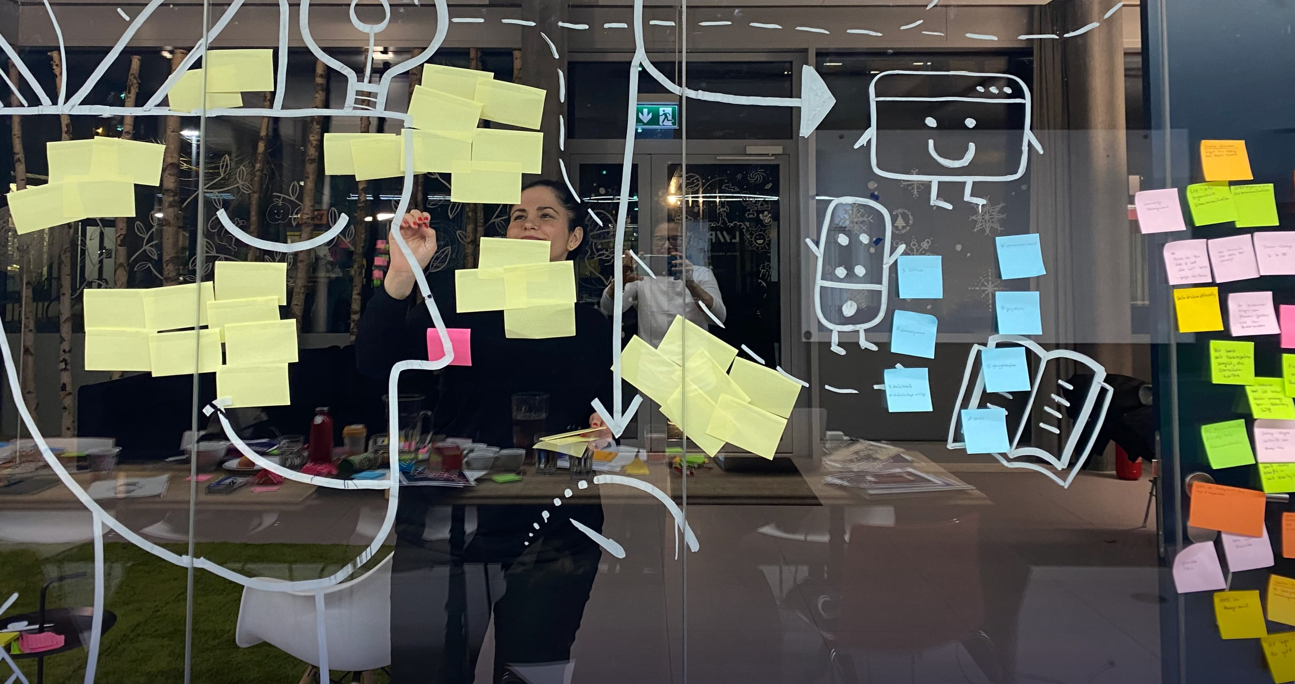 a smiling woman pins post-it notes pinned to a glass wall