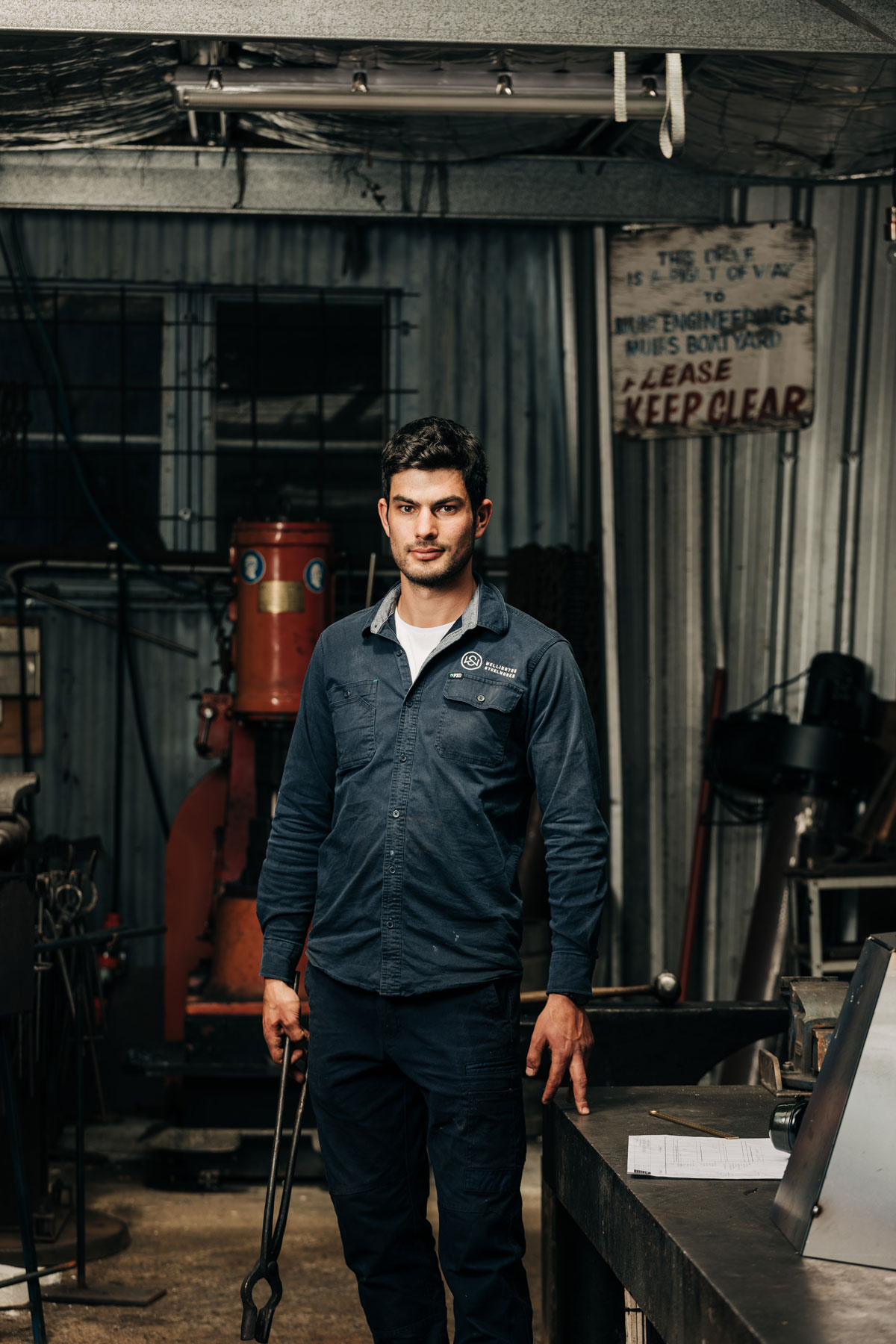 taig simms standing up in wellington steelworks overalls