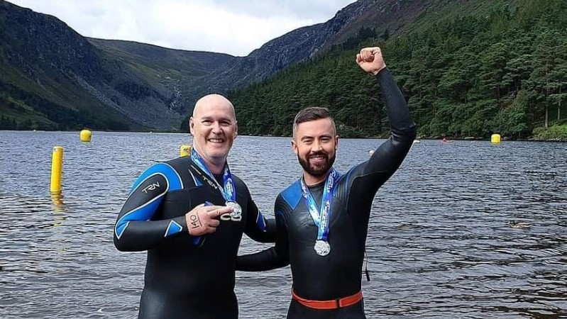 Deric The TV3/Virgin TV weatherman celebrating with an unknow swimmer and their medals after the Glendalough race