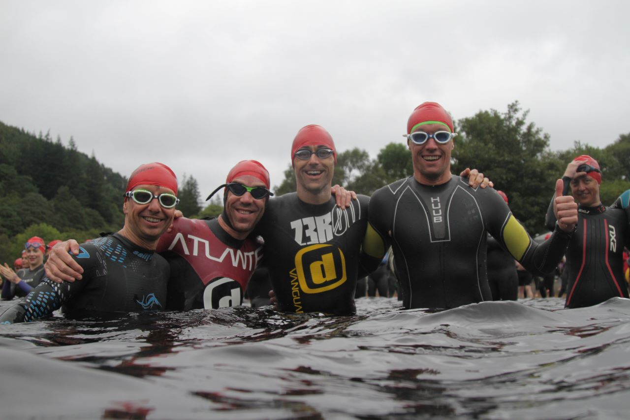 Open water swimmers celebrating in the water after completing their swim.