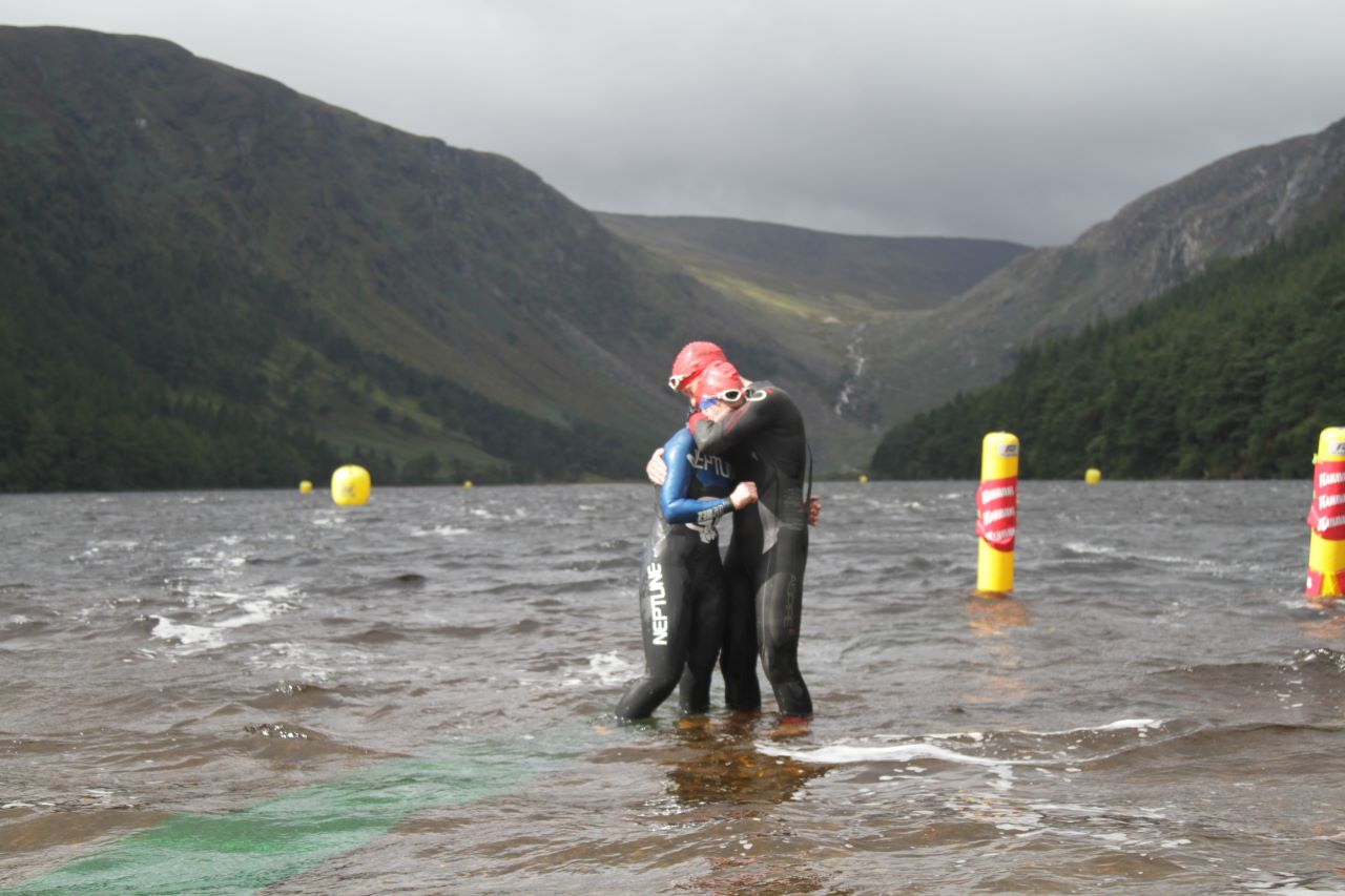 Two Open water swimmers embracing in the lake after completing their races event with Open Water Swimmer