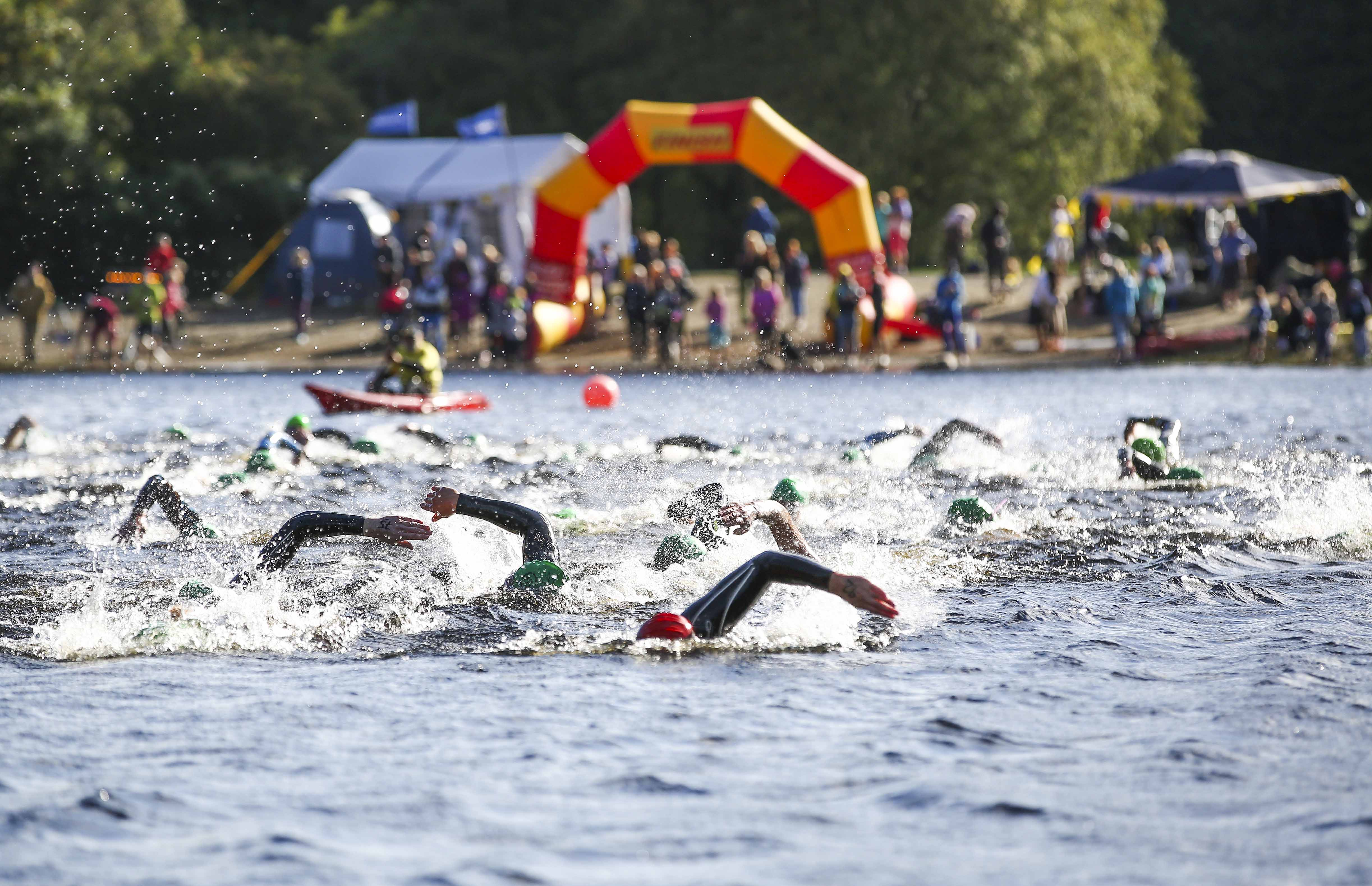 A group of open water swimmers racing away from the starting line at an Open Water Swimmer swim series.