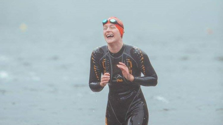 Ecstatic Open Water Swimmer competitor coming out of the water after completing a race