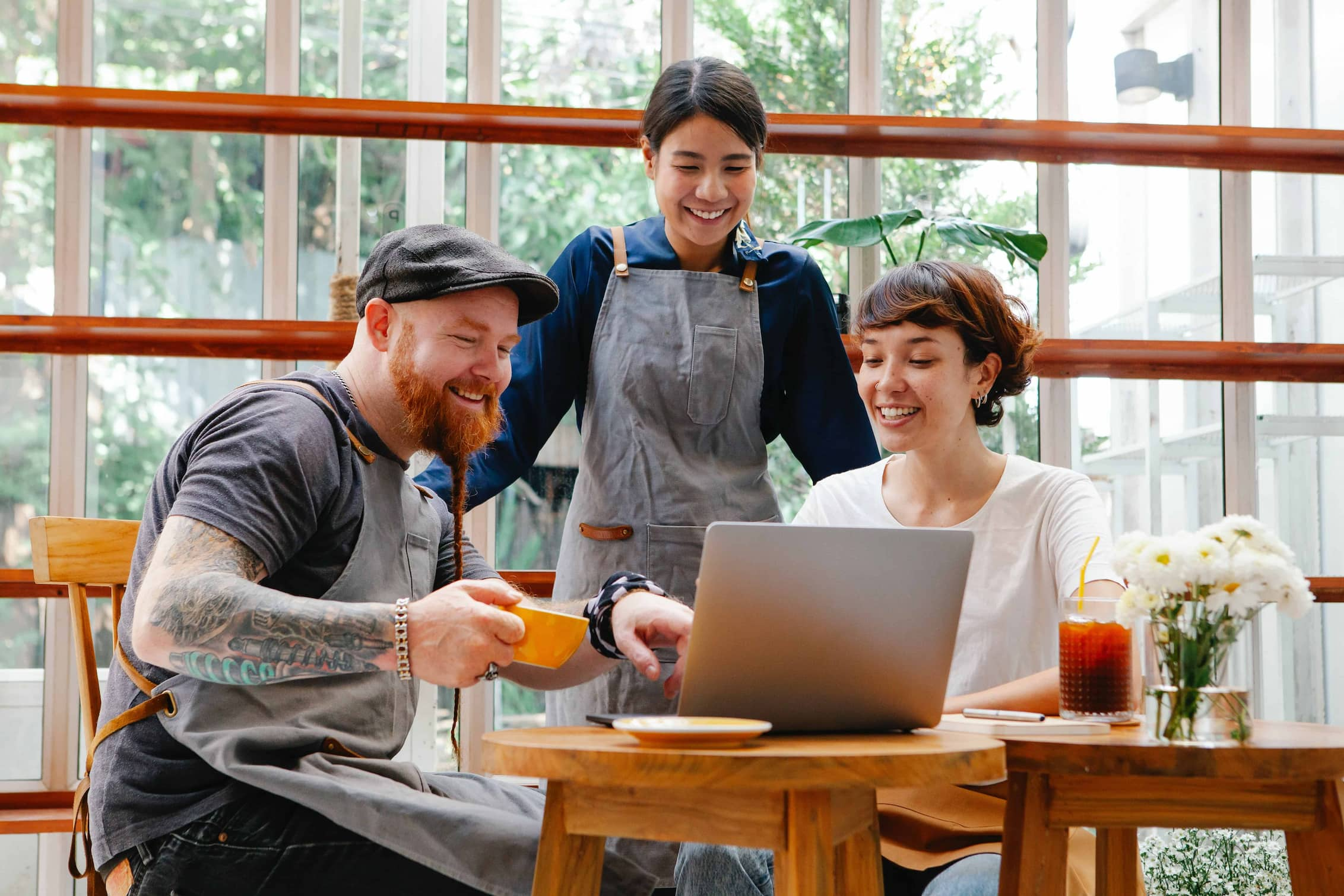 Small business owners gathered around laptop