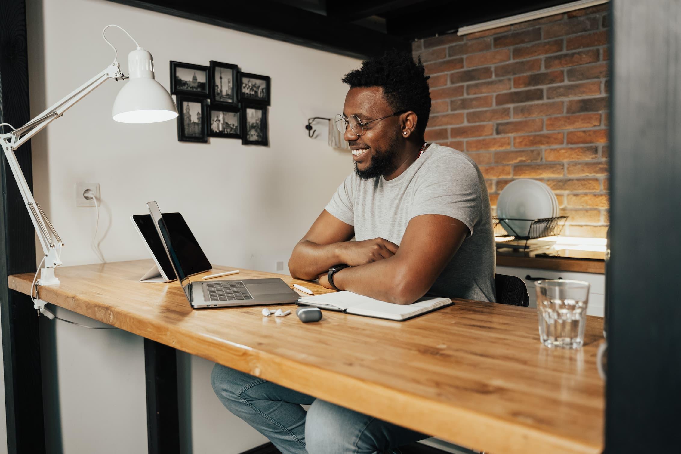 Man smiling at computer at a desk