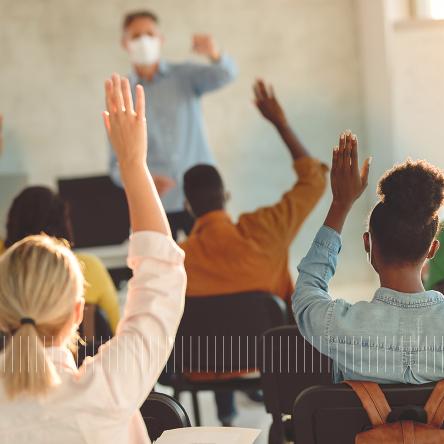 college students raising hands