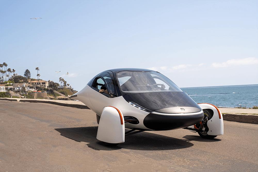 Aptera solar vehicle driving alongside the ocean