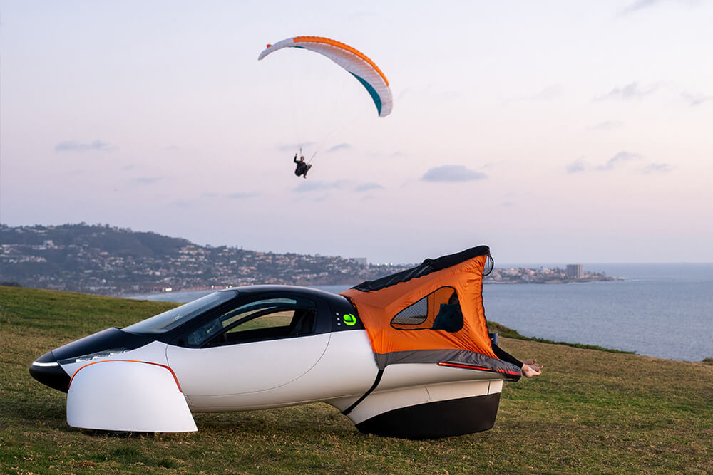 Aptera vehicle with a paraglider in the background