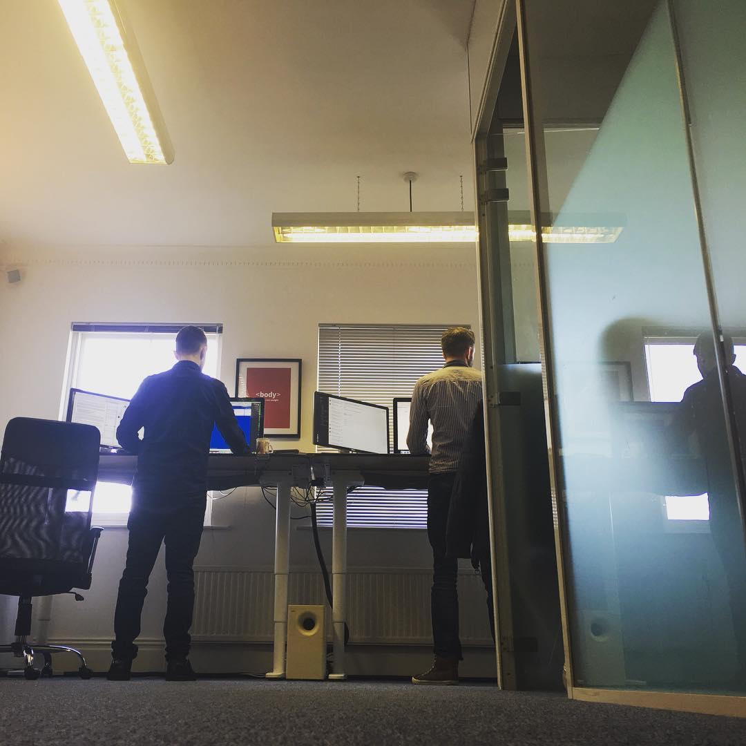 Dave and Matt standing at their standing desks