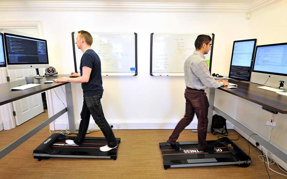 DEvelopers on standing desks with treadmill