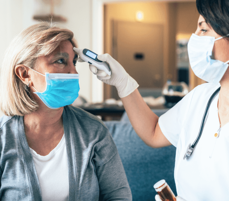 Nurse taking woman's temperature on forehead