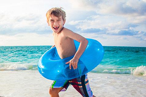 Child running on Grace Bay beach with inner tube