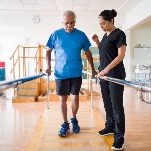 Physical therapy patient walking using parallel bars with the the help of physical therapist