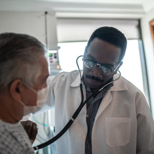 Doctor with lab coat listening to patient's heart with stethoscope