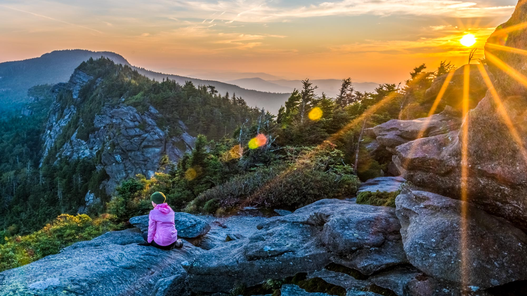 Person in pink coat sitting on a rock on the side of a mountain, sunrise in the background, looking over blue ridge mountains