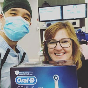 Blooming Family Dental Smiling Patient holding Oral-B tooth brush box with Dr Chang