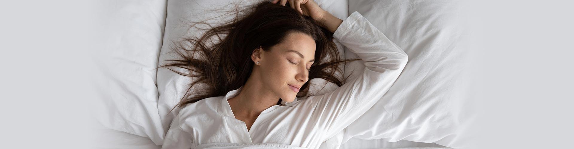 Sleeping woman on white sheets