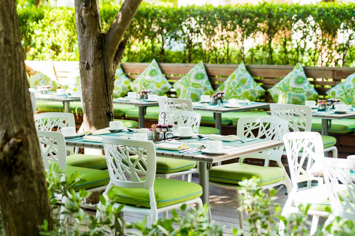 Complimentary breakfast is served in a pretty courtyard surrounded by tropical plants.