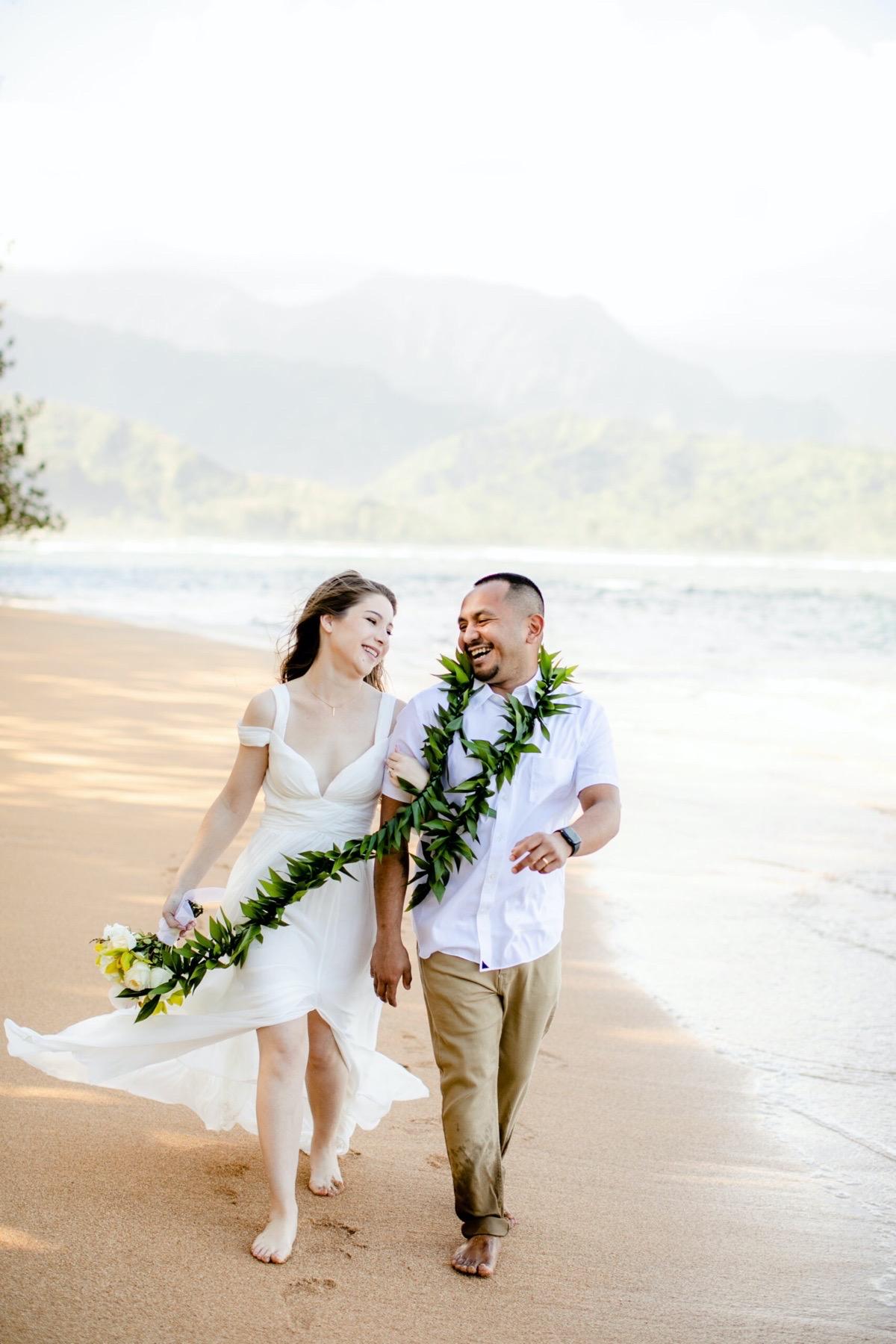 Couple walking on a beCh in Kauai.