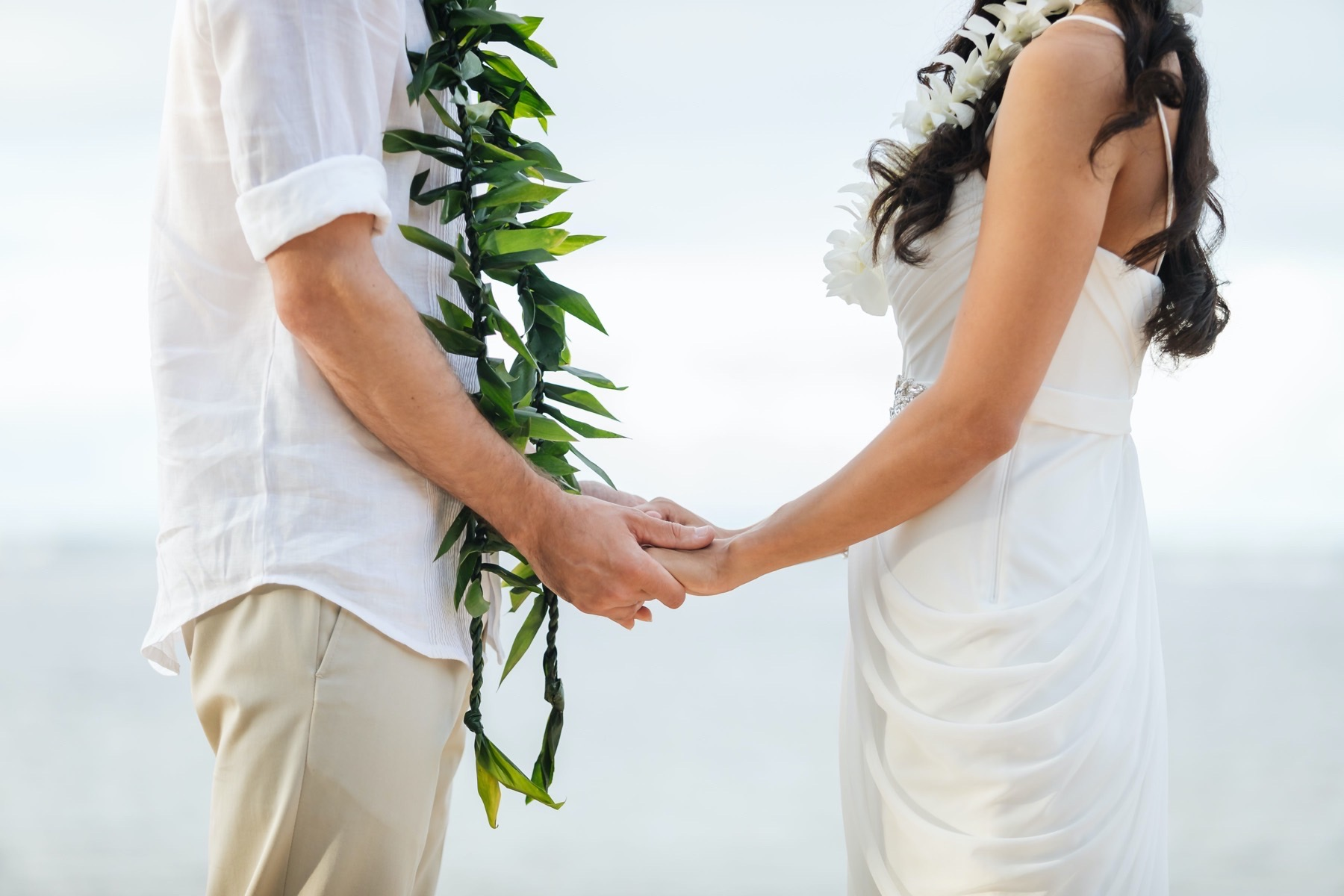 Man and Woman holding hands wearing Leis.