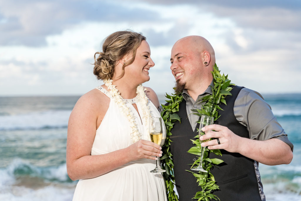 Husband and wife drinking champagne after wedding in Hawaii.