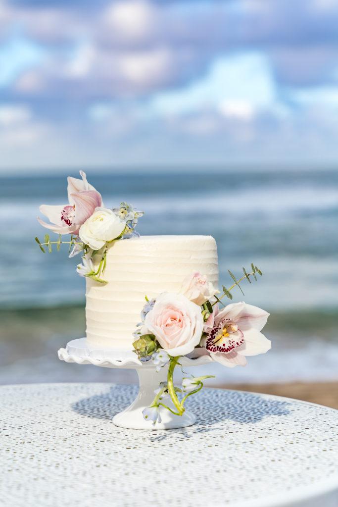 Wedding cake on the beach in kauai.