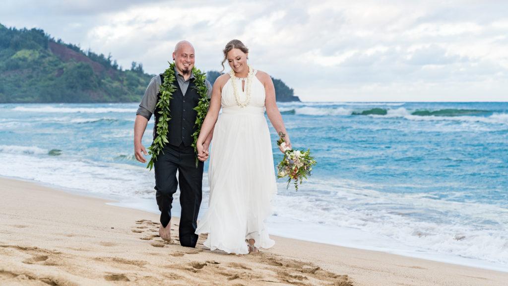 Bride and Groom walking on a beach in Kauai.