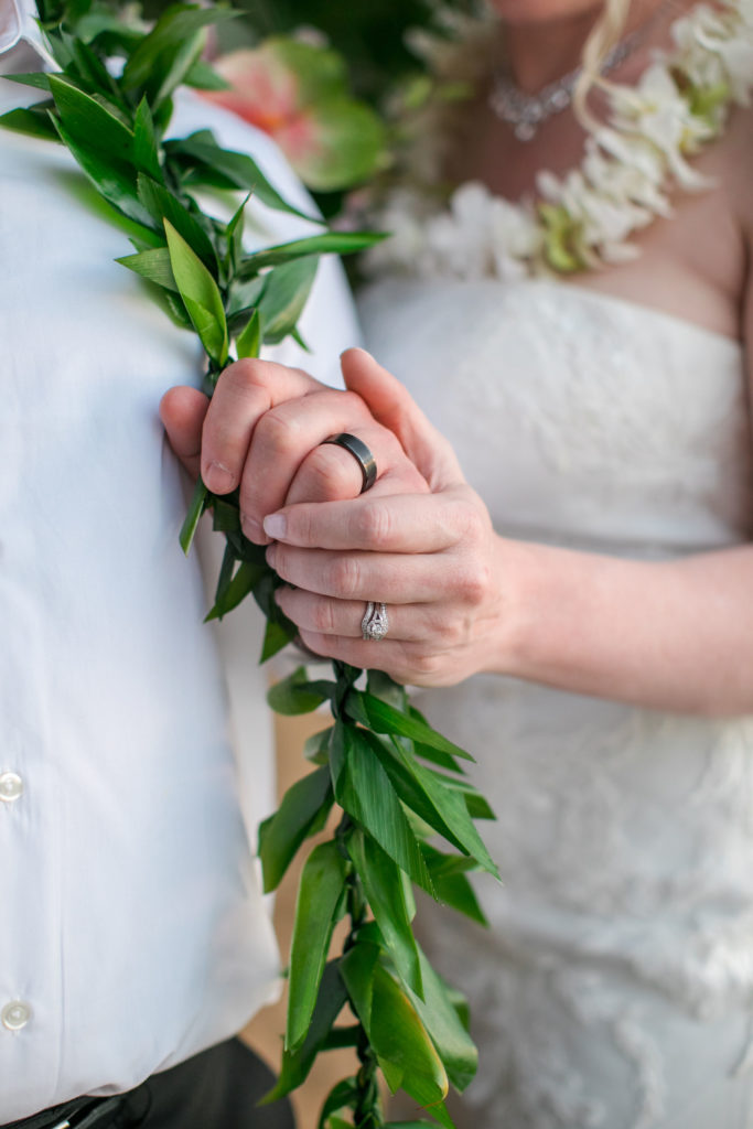 Closeup of wedding rings on husband and wife.
