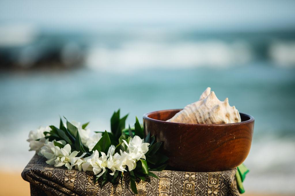 Lei and seashell on the beach.