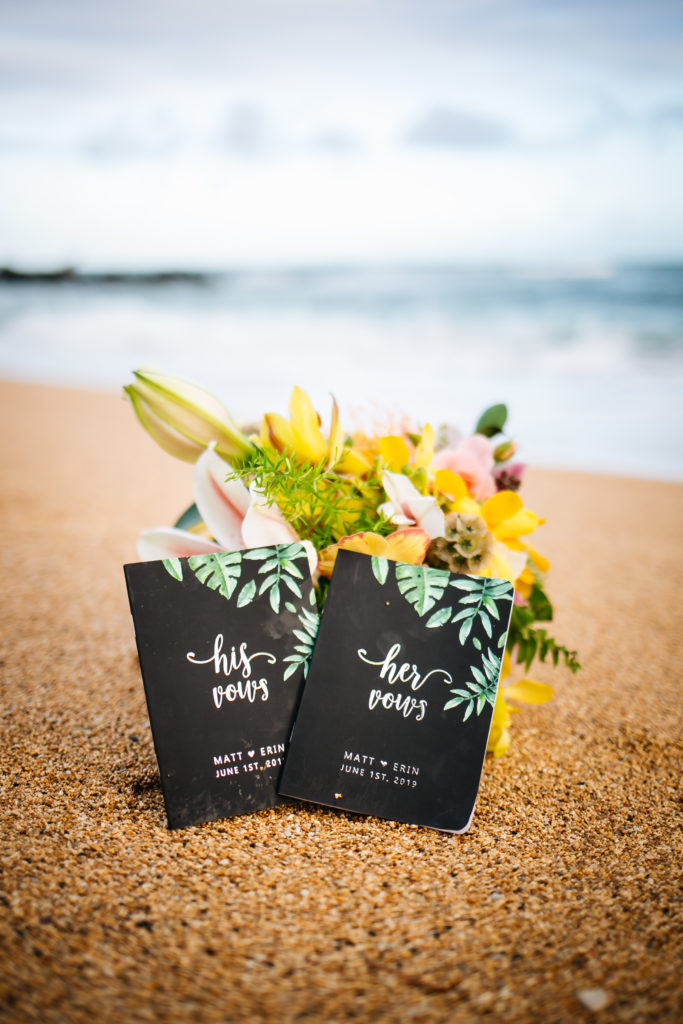 His and hers vow books in sand.