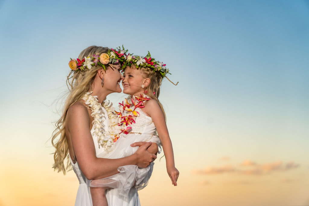 Bride and daughter at sunset on the beach.
