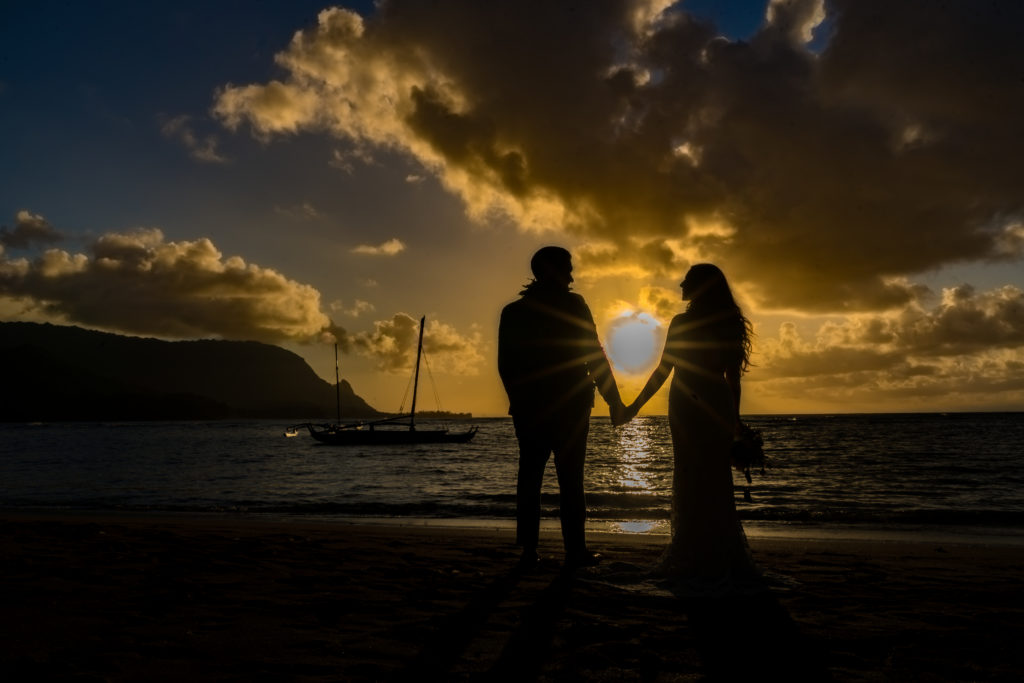 Bride and groom in front of the ocean at sunset.