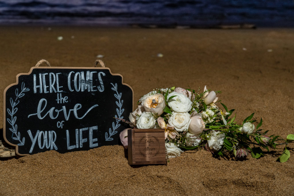Flowers and sign in the sand for wedding.