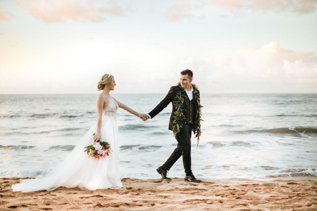Bride and groom walk on the beach.