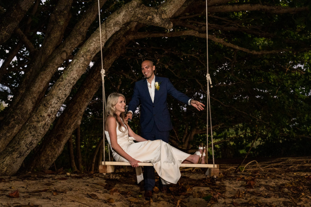 Bride and groom on the beach under a tree.