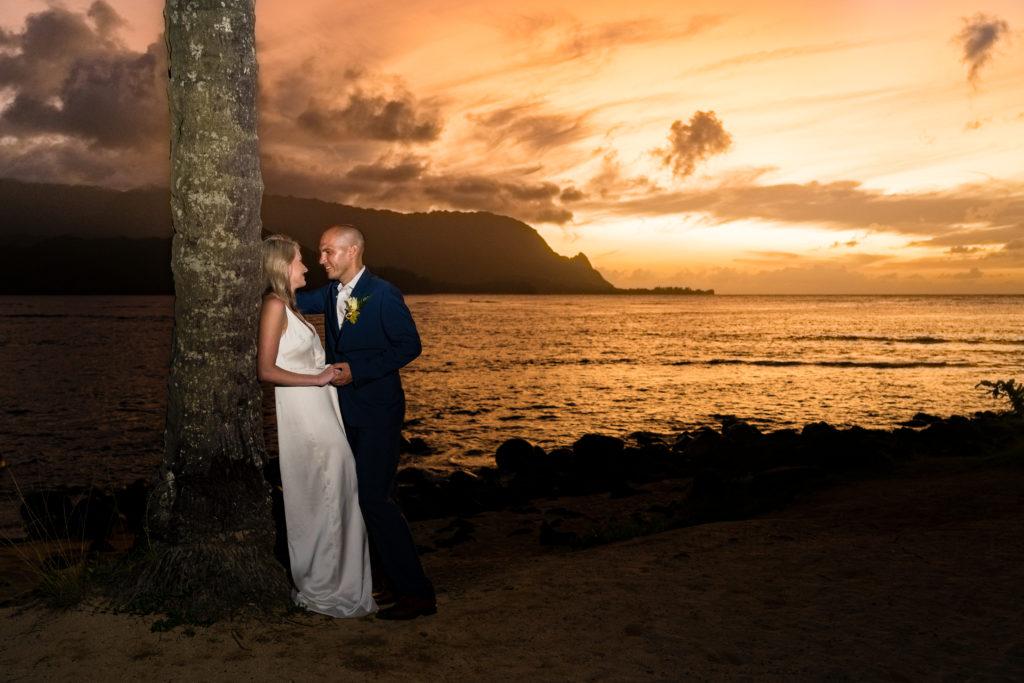 Bride on groom posing at sunset.