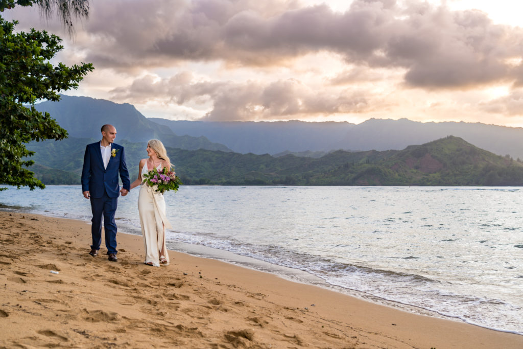 Bride and groom walking on the beach in Kauai.